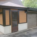 Brown door with glass windows in the front of a home with wood style siding.