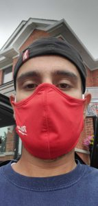 Man looking into camera for a selfie wearing a red mask to protect himself from COVID-19.