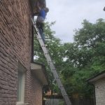 A technicians standing on a tall ladder while repairing eavestrough on a roof.